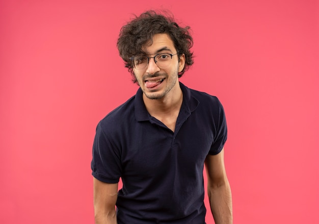 Young joyful man in black shirt with optical glasses stucks tongue out isolated on pink wall