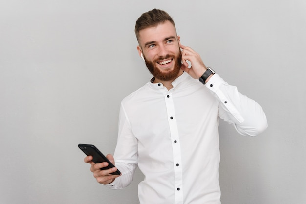 灰色の壁に隔離されたイヤポッドと携帯電話を使用しながら笑っている若いうれしそうな男