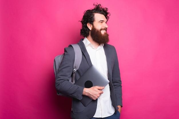 バックパックと新しいコンピューターを持った若いうれしそうな男は笑顔で彼の後ろにピンクの壁で目をそらしている
