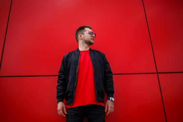 街の赤い金属の建物の近くでポーズをとるtシャツのファッショナブルな黒のジャケットのtシャツで前向きな笑顔でひげを生やした若いうれしそうな男。通りで幸せな都会の男。紳士服