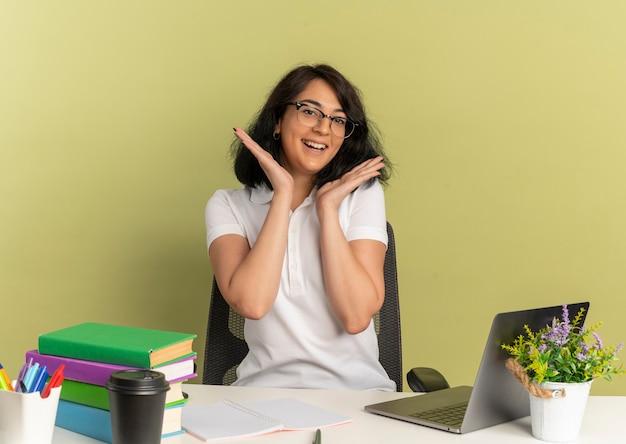 안경을 쓰고 젊은 즐거운 예쁜 백인 여학생은 학교 도구와 함께 책상에 앉아 복사 공간 녹색에 얼굴을 손을 보유