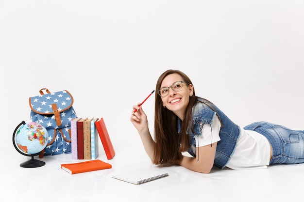 Young joyful pretty woman student in denim clothes, glasses holding pencil notebook lying near globe, backpack, school books isolated