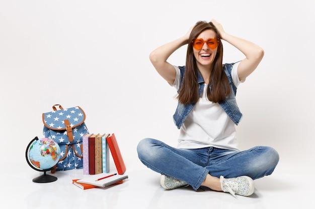 Молодая радостная симпатичная студентка в красных сердечных очках, цепляясь за голову, сидит рядом с земным шаром, рюкзаком, школьными учебниками, изолированными на белой стене