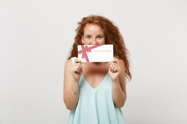 白い壁の背景、スタジオの肖像画に分離されたポーズでカジュアルな明るい服を着た若いうれしそうな赤毛の女性の女の子。人々のライフスタイルの概念。コピースペースをモックアップします。ギフト券で口を覆う。