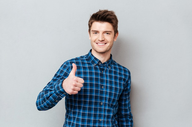 Young joyful student man holding thumb up isolated