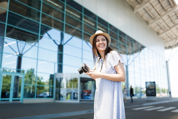 Young joyful traveler tourist woman holding retro vintage photo camera, looking aside at international airport