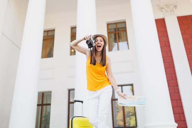 Молодая радостная туристическая женщина путешественника в повседневной одежде с чемоданом, карта города фотографирует на открытом воздухе ретро винтаж фотоаппаратом. девушка выезжает за границу на выходные. туризм путешествие образ жизни.
