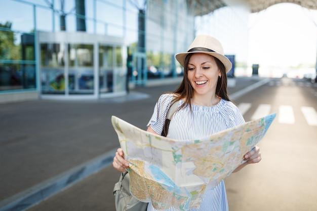 Молодой радостный путешественник турист женщина в шляпе с рюкзаком держит бумажную карту, стоя в международном аэропорту