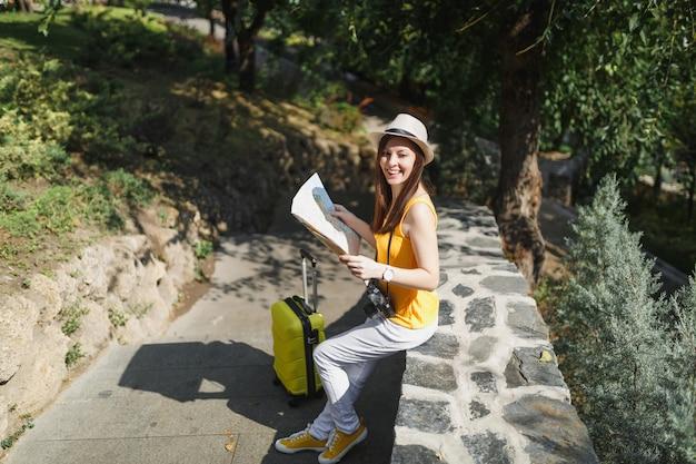 黄色い服を着た若い楽しい旅行者の観光客の女性、スーツケースの帽子は、屋外の街の石の上に座って都市地図を保持します。週末の休暇に旅行するために海外に旅行している女の子。観光の旅のライフスタイル。