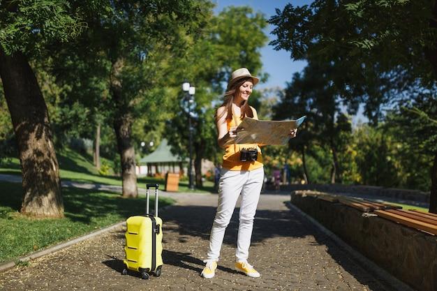 노란색 여름 캐주얼 옷을 입은 젊고 즐거운 여행자 관광 여성, 여행 가방 도시 지도가 있는 모자는 도시 야외에서 산책합니다. 주말 휴가를 여행하기 위해 해외로 여행하는 소녀. 관광 여행 라이프 스타일.