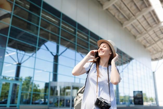 レトロなビンテージ写真カメラを持つ若い楽しい旅行者の観光客の女性が携帯電話の友人に話します
