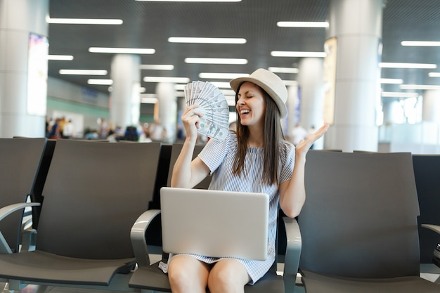 Giovane turista gioiosa viaggiatrice che lavora al computer portatile, tiene in mano un pacco di dollari, denaro contante spalmato le mani aspetta nella hall dell'aeroporto