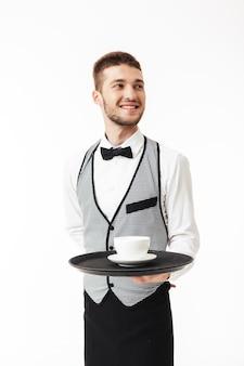 幸せにしながら手にコーヒーのカップと制服保持トレイで若いうれしそうなウェイター