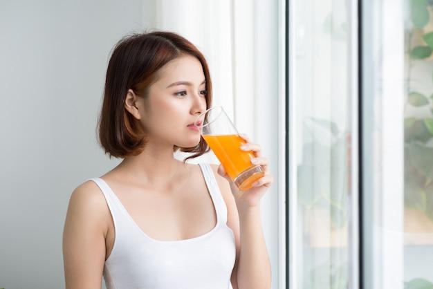 オレンジジュースを飲み、窓の近くに立っている若いうれしそうな女性