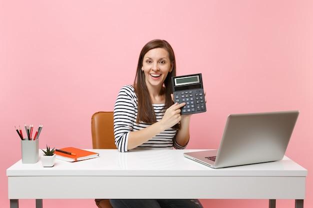 パステルピンクの背景に分離された現代的なpcラップトップで座ってプロジェクトに取り組んでいる間電卓を保持している若いうれしそうな女性。業績ビジネスキャリアコンセプト。スペースをコピーします。