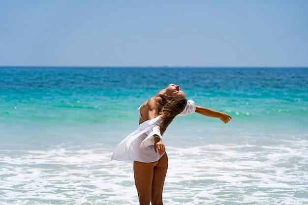바다와 자유의 행복과 평온한 개념을 즐기는 비키니와 흰색 셔츠를 입은 젊은 즐거운 여성