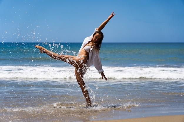 바다와 자유를 즐기는 비키니와 흰색 셔츠에 젊은 즐거운 여자. 행복과 평온한 개념입니다.