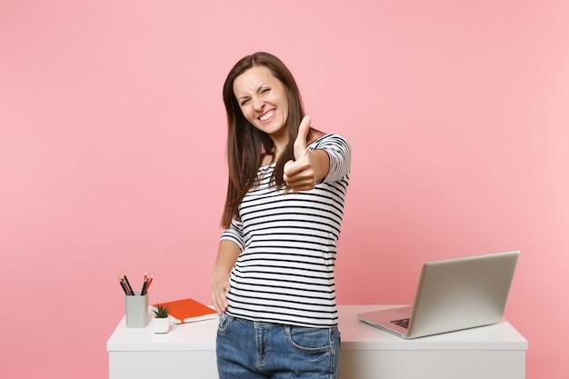 パステルピンクの背景で隔離のラップトップと白い机の近くに立って、親指を立てる仕事を示すカジュアルな服を着た若いうれしそうな女性。業績ビジネスキャリアコンセプト。広告用のスペースをコピーします。