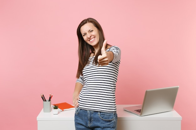 ノートパソコンで白い机の近くに立って、親指を立てる仕事を示すカジュアルな服を着た若い楽しい女性
