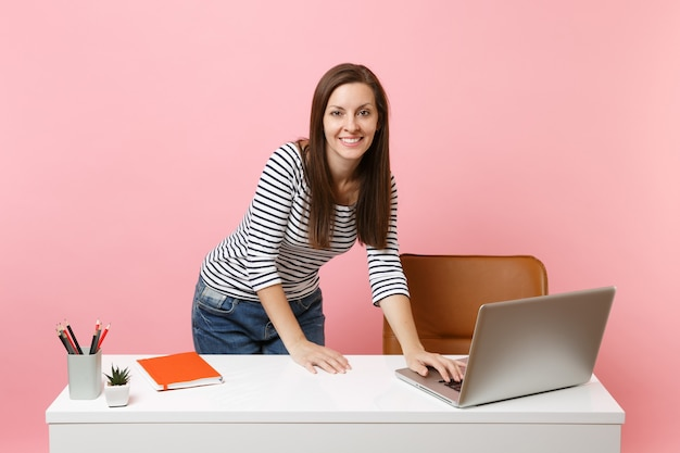 パステルピンクの背景で隔離の現代的なpcラップトップで作業している白い机の近くに立っているカジュアルな服を着た若いうれしそうな女性。業績ビジネスキャリアコンセプト。広告用のスペースをコピーします。