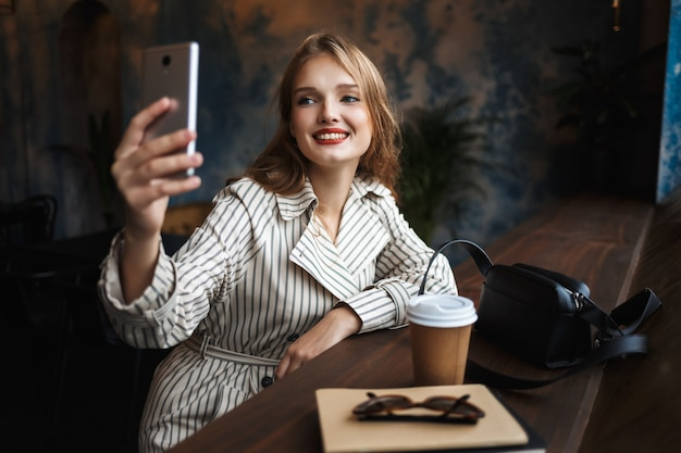 Young joyful woman in striped trench coat happily taking photos on cellphone with little black handbag and coffee to go near while spending time in modern cafe