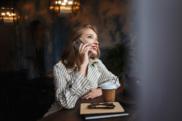 Young joyful woman in striped trench coat talking on cellphone happily
