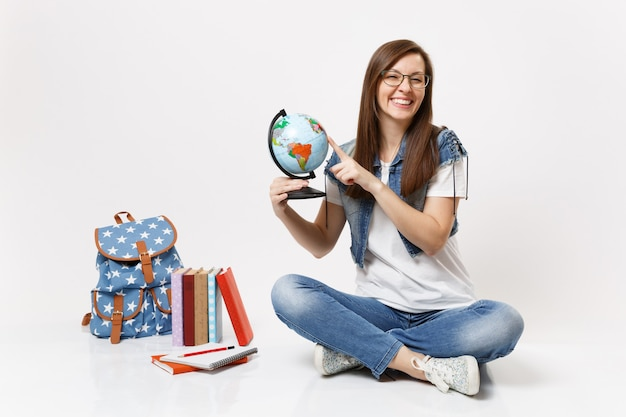 Young joyful woman student in glasses holding world globe pointing finger on countries sitting near backpack, school books isolated