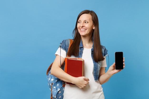 책가방을 들고 책가방을 들고 데님 옷을 입은 젊고 즐거운 여학생, 파란색 배경에 격리된 빈 검은색 빈 화면이 있는 휴대전화. 고등학교 대학 대학에서 교육.