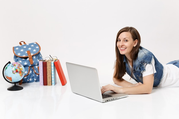 Молодая радостная студентка в джинсовой одежде, работающая на портативном компьютере, лежащем рядом с земным шаром, рюкзаком и изолированными школьными учебниками