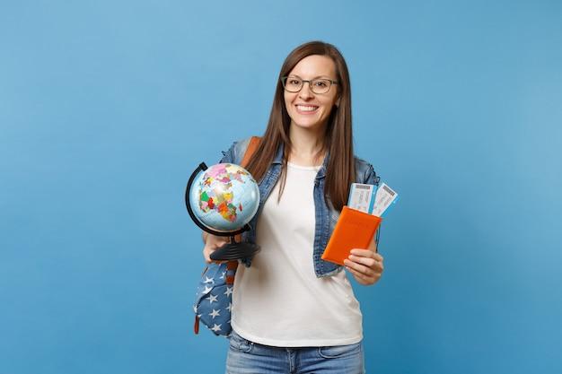 Молодой радостный студент женщины в очках с рюкзаком, держащим перчатку мира, паспорт, билеты на посадочный талон, изолированные на синем фоне. обучение в вузе за рубежом. концепция полета авиаперелета.