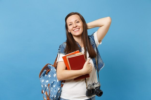 Young joyful woman student with backpack and retro vintage photo camera on neck keeping hand on head hold school books isolated on blue background. education in high school university college concept.