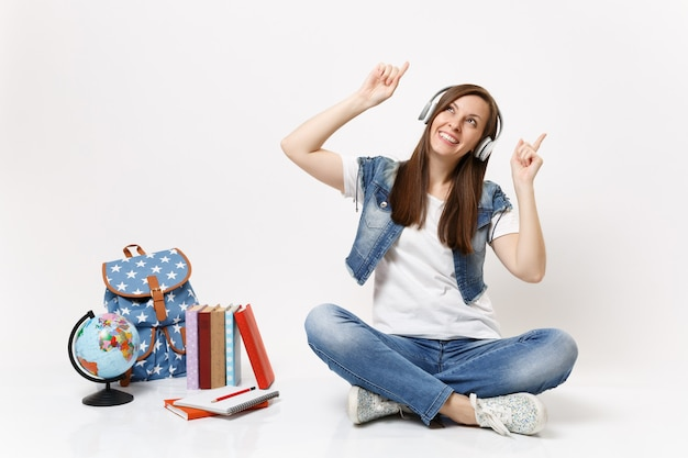 Young joyful woman student with headphones listening music pointing index fingers up sitting near globe backpack school books isolated