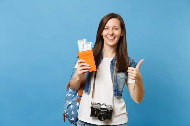 Молодая радостная студентка с ретро винтажной фотокамерой на паспорте владения шеи, билетами на посадочный талон, показывающими большой палец вверх изолированным на синем фоне. обучение в вузе за рубежом. авиаперелет.