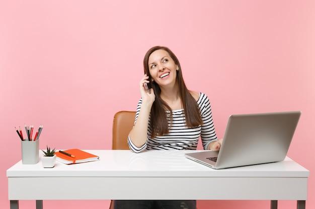 젊은 즐거운 여성은 휴대전화로 이야기하고 즐거운 대화를 나누며 파스텔 핑크색 배경에 격리된 pc 노트북을 들고 흰색 책상에서 일합니다. 성취 비즈니스 경력 개념입니다. 공간을 복사합니다.