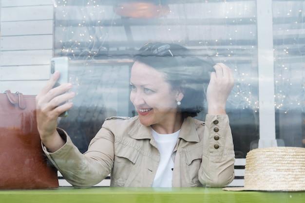 カフェのテーブルでビデオリンクで電話で話している若いうれしそうな女性。