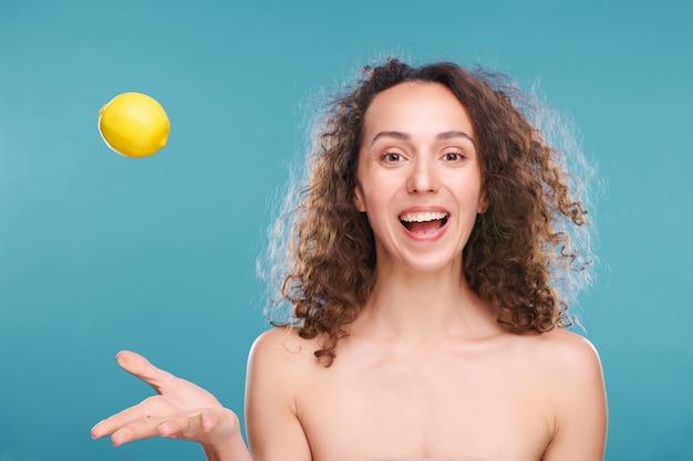 裸の肩と暗い巻き毛の若い楽しい女性は、新鮮なレモンを投げて、幸せを表現しながら手でそれをキャッチします
