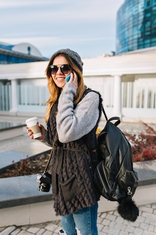 大都市で晴れた寒い日に歩いて行くコーヒーを持つ若いうれしそうな女性。暖かい冬の腫れたセーター、モダンなサングラスを身に着けているきれいな女性が電話で話して、カメラとバッグで震え、幸せ。