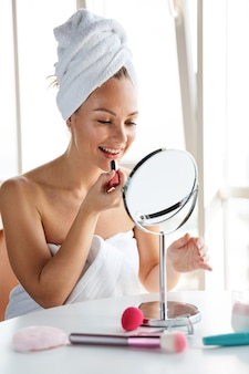 シャワーの後に鏡を見ながら化粧をしている白いタオルに包まれた若いうれしそうな女性