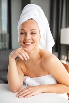 シャワーの後部屋に座って笑っている白いタオルに包まれた若いうれしそうな女性