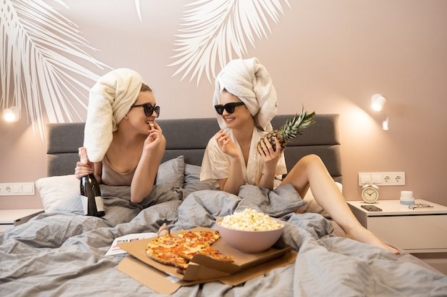 Young joyful women lying on bed, eating popcorn and holding champagne bottle and pineapple. girlfriends wear glasses and wrapped bath towels. concept of girls party at home. bedroom in modern flat