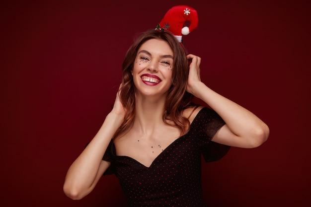 우아한 옷을 입고 즐거운 갈색 머리 아가씨와 친구와 함께 멋진 새해 파티를 기뻐하는 휴가 후프