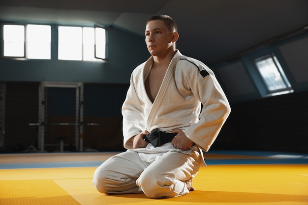 Young judo caucasian fighter in blue kimono with black belt posing confident in the gym, strong and healthy.