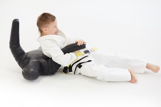 Young judoist practicing technique on mannequin