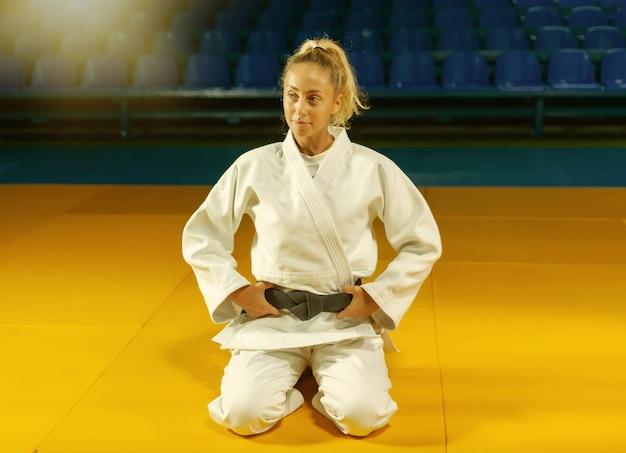 スポーツホールの床に座っている黒帯の白い着物を着た若い柔道家の女性