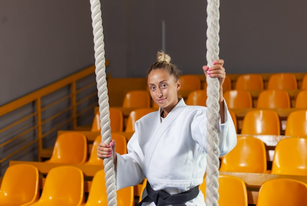 Young judoka woman in white kimono and black belt posing in the sports hall