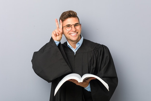 Молодой юрист держит книгу, показывая знак победы и широко улыбается.