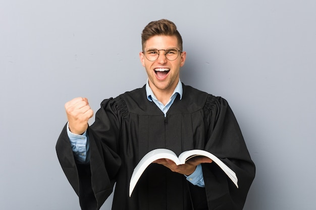 Young jurist holding a book cheering carefree and excited. victory concept.