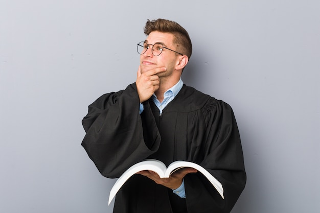 Young jurist holding a book looking sideways with doubtful and skeptical expression.