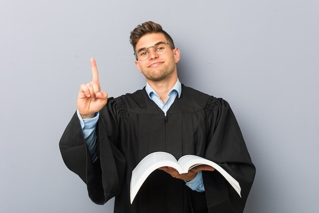 Young jurist holding a book showing number one with finger.