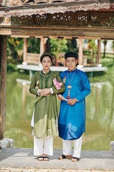 젊은 막 결혼한 베트남 부부는 전통 아오자이 드레스를 입고 연꽃과 함께 야외에 서 있다